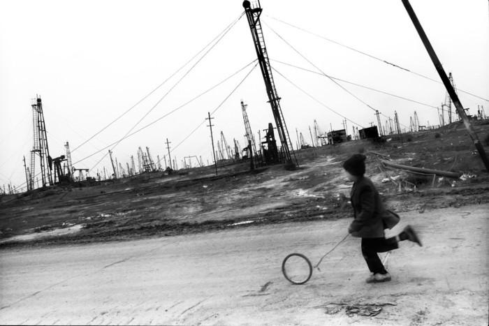 Fotoğraf: Rena Effendi. Doğduğu Balakhani köyünün petrol alanlarında kendi yaptığı oyuncağıyla oynayan çocuk. Azerbaycan. 2003